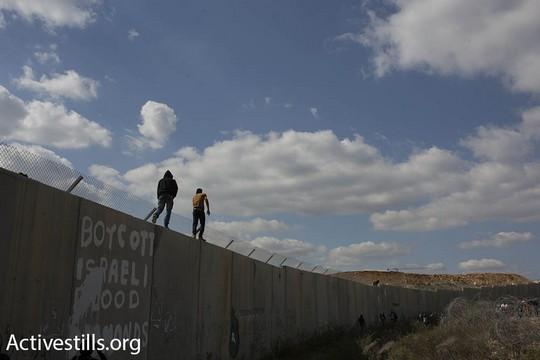 אני עומד על החומה. מפגינים במהלך הצעדה לציון 12 שנות מאבק עממי נגד החומה והכיבוש בבלעין (פאיז אבו-רמלה/אקטיבסטילס)