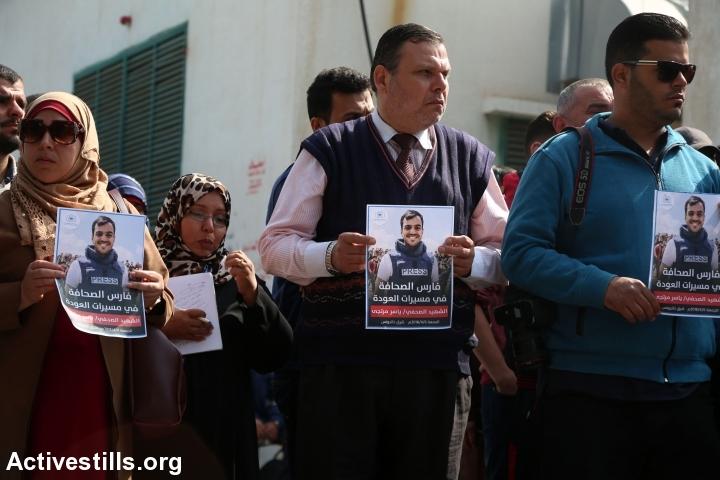 עיתונאים, חבריו של יאסר מורתג'א, נושאים את תמונתו במהלך מסע הלוויתו של הצלם שנהרג מאש חיילים במהלך צעדת השיבה. עזה, 7 באפריל 2018. (מוחמד זאנון / אקטיבסטילס)