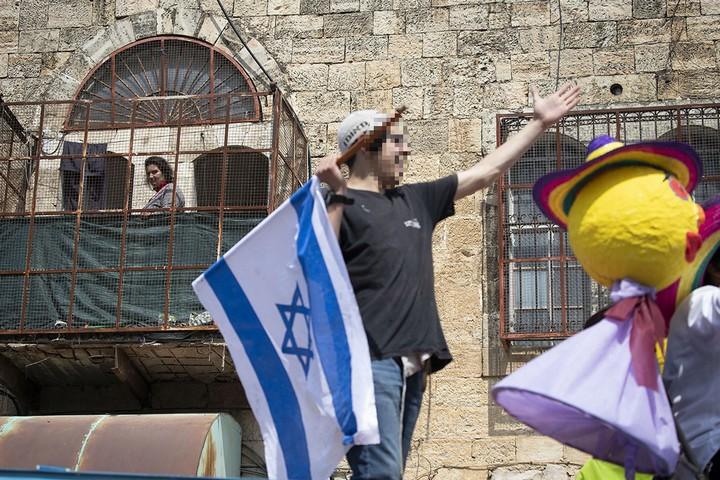 היהודים צוהלים ברחוב, הפלסטינים בכלובים שלהם בבתים. רחוב השוהדא, פורים 2019, חברון. (אורן זיו)