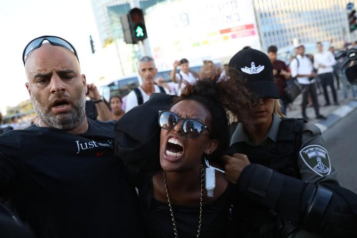 שוטרת עוצרת מפגינה במחאת יוצאי אתיופיה נגד אלימות משטרתית בתל אביב, 3.7.19 (אורן זיו / אקטיבסטילס)