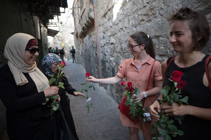 ישראליות מחלקות ורדים לערביות בעיר העתיקה, ביום ירושלים ב-2017 (צילום: נתי שוחט / פלאש90)