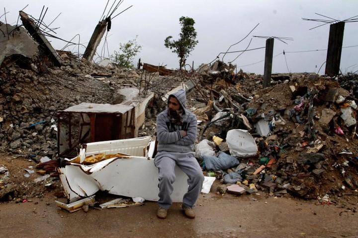 יש לך מזוודות שיכולות להכיל את הקירות? גבר יושב ליד הריסות ביתו אחרי הפצצה בעזה (צילום: עבד רחים ח'טיב / פלאש 90)