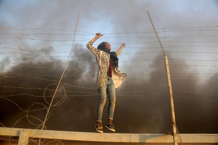 """222 פלסטינים נהרגו מאש חיילים במחאות """"מצעד השיבה"""". 11 מקרים נחקרו. צעירה פלסטינית על הגדר בין עזה לישראל במהלך הפגנות """"צעדת השיבה"""" (צילום: מוחמד זאנון / אקטיבטילס)"""