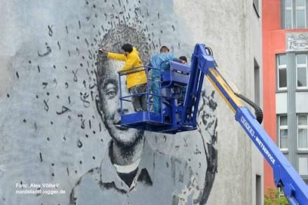 יאזן חלוואני וסטודנטים מקומיים מציירים בעזרת מנוף. צילום: אלכס פולקל
