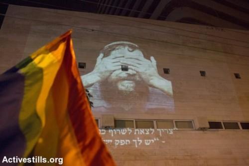 """דגל גאווה במהלך הפגנת מחאה נגד ההסתה הממשלתית נגד פלסטינים וקהילת הלהט""""ב, בעקבות הרצח במתעד הגאווה ורצח משפחת דוואבשה בכפר דומא (אורן זיו/אקטיבסטילס)"""