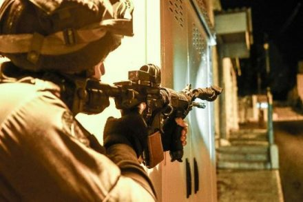 """חייל צה""""ל דורך את נשקו בכפר פלסטיני בגדה המערבית (צילום: דובר צה""""ל)"""