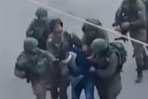 חיילים מכים, בועטים ונותנים ברכיות לפלסטיני אזוק ומכוסה עיניים בחברון. 18 בדצמבר 2017 (צילום מסך מתוך סרטון ISM)