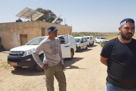 שוטרים מלווים את אנשי רשות מקרקעי ישראל לחלוקת צווי פינוי והריסה לכל מבני ותושבי הכפר. 21 במרץ 2018 (רא'אד אבו אלקיעאן)