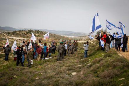 """המלחמה על ההגמוניה. פעילי """"שלום עכשיו"""" מפגינים מול תושבי המאחז נתיב האבות בקריאה לקיים את החלטת בית המשפט לפנות את ההתנחלות. (גרשון אלינסון / פלאש 90)"""