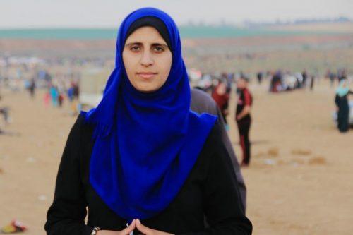 מסקרת את ההפגנות, אבל המבט לעבר כפר שבו נולדה משפחתה. אסרה אע'יר ליד הגדר בעזה (צילום באדיבות אסרה אע'יר)