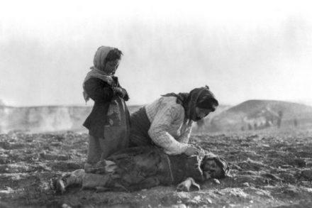 אשה כורעת לצד ילד פגוע בזמן שואת הארמנים (צילום: American Committee for Relief in the Near East)