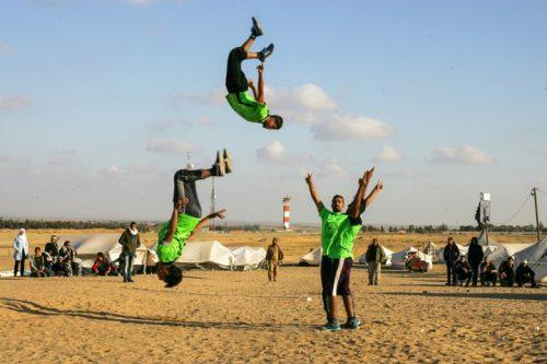"""""""אנשים בעזה צמאים לשינוי, אפילו משהו קטן"""". צעירים עזתים מבצעים פרקור מול הגבול עם ישראל (צילום: עבד רחים רח'מן / פלאש 90)"""