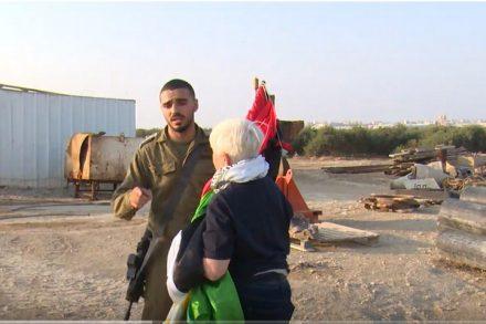 החיילים מנעו מהמפגינים להגיע לנקודת תצפית על עזה, אבל הם שוחחו עם המפגינים הפלסטינים בטלפון.. חייל עוצר מפגינה להגיע לתצפית על הגדר (צילום מסך: דוד ריב)