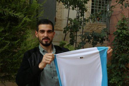 כראם קוואסמי, פלסטיני בן 22 מחברון, מחזיק את החולצה שלבש כשחייל ישראלי ירה בו בגבו בכדור ספוג (צילום: MEE/Alaa Daraghmeh)